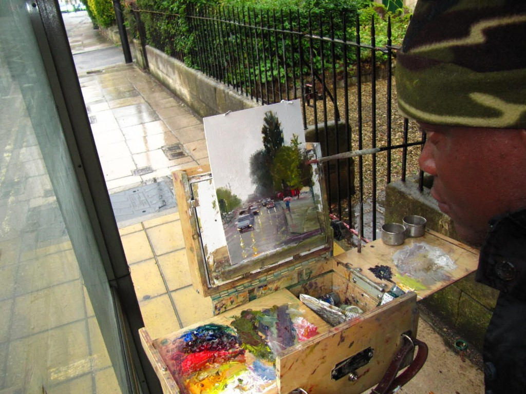 Adebanji painting on the street of Bath on a Rainy Day
